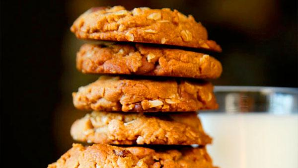 A stack of Peanut Butter Oatmeal Chocolate Chip Cookies with a glass of milk.